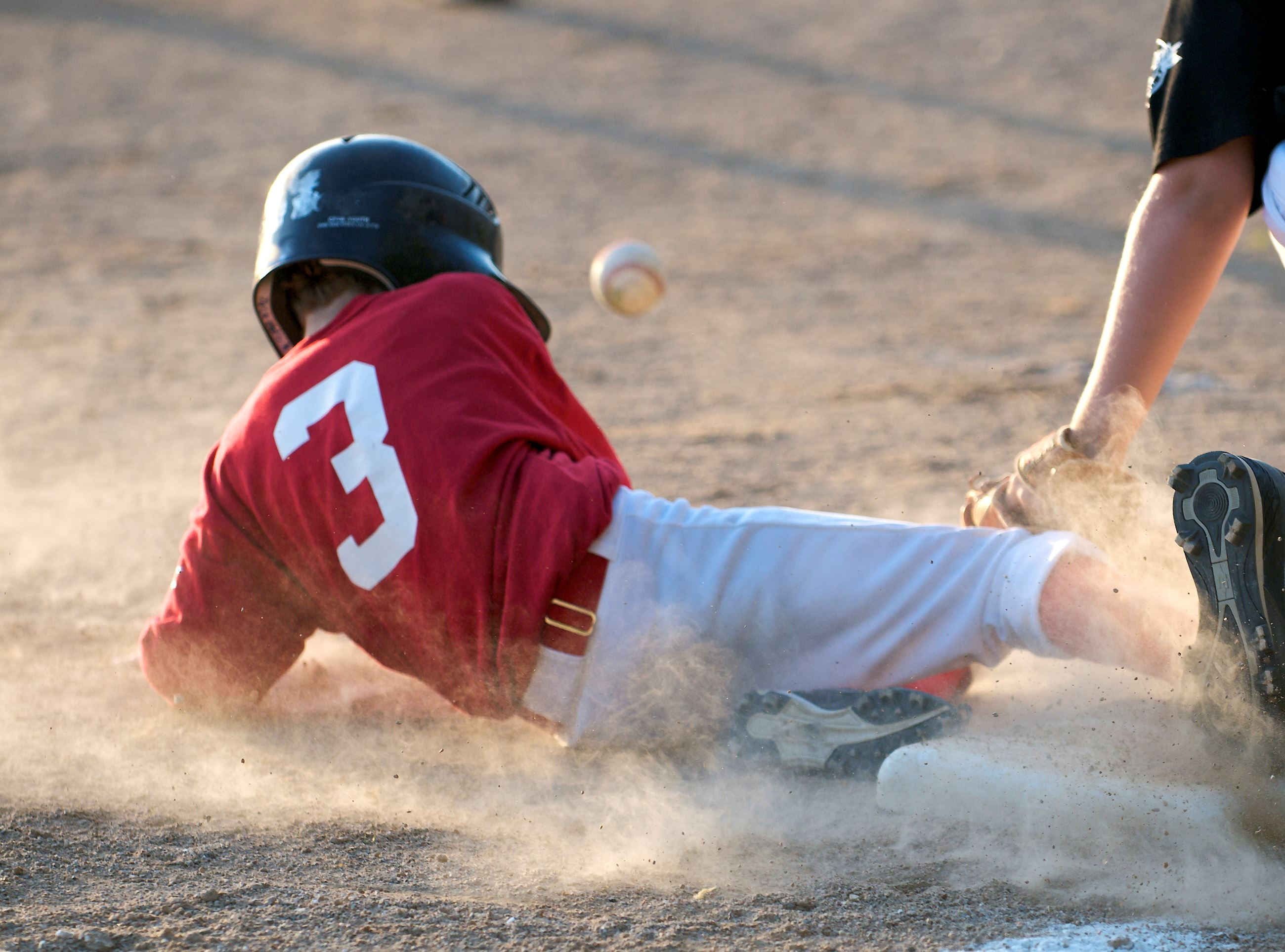 A baseball player sliding into a base